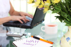 Working at home. Woman working at home composition. Shallow DOF wih focus on writing and pen in front stock image