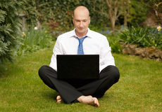 Working from home. Successful businessman in white shirt and tie working cross legged on a laptop in a garden Royalty Free Stock Image