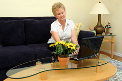 Working from home. A mature woman working from home or paying bills on a computer Royalty Free Stock Image