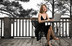 Working From Home. Young woman in pretty black dress smiles while working on her laptop. Taken on the back deck of a bayside home in Panacea, Florida royalty free stock photo