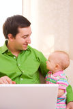 Working from Home. Father working on laptop from home while babysitting his daughter Stock Photos