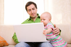 Working from Home. Father working on laptop from home while babysitting his daughter royalty free stock photography