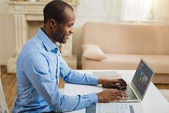 Inspired man working from home. Working from home. Attractive cheerful afro-american man grinning and working on the laptop while sitting at the table and a Stock Images