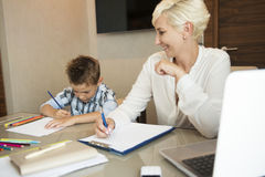 Working home blonde businesswoman with her young son drawing stock images