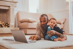 Serious man working and babysitting his kid. Working from home. Concentrated young father working on his laptop and babysitting his little son stock photography