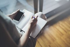 Working at home concept. Entrepreneur business woman writing and taking notes using her mobile phone and paper note book.  royalty free stock photos