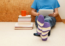 Working from home. Man relaxing in bed using digital tablet, close up on male foots in socks Stock Images
