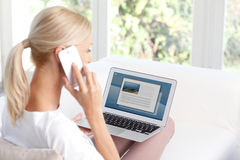 Working at home. Portrait of casual woman making call with mobile phone while sitting at home and working online with laptop. Looking for places to travel on royalty free stock photography