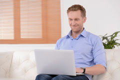 Working at home. Young red hair businessman sitting on the couch Stock Photos
