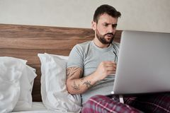 Working in hotel room. man using laptop computer while sitting i. Working in hotel room. serious man using laptop computer while sitting in bed royalty free stock images