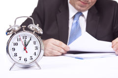 Working hours. A businessman is working behind a clock Stock Photos