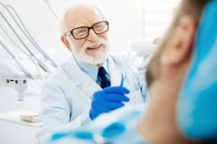 Close up of experienced dentist with false teeth in hand. Working hours. Close up of experienced dentist sitting near the patient while holding false teeth with Stock Images