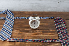 Working hours day concept. Ties and vintage alarm clock. Stock Images