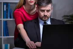 Working after hours. Handsome men working after hours with his young pretty secretary royalty free stock images