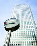 Working hours. The iconic Canary Tower in the London Docklands business district with a clock in the foreground marking the time Royalty Free Stock Photo
