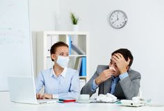 Working during illness. Image of sick businessman with tissue looking at laptop screen with his colleague wearing mask neaer by in office Stock Photo