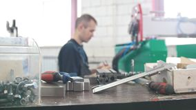 Working instruments in front of electrician in overalls is working with energy panel and machinery equipment on the. Plant, close up stock footage