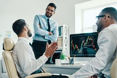 Working with investments. Group of young modern men in formalwear analyzing stock market data while working in the office royalty free stock image