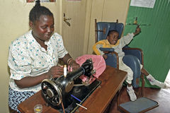 Working Kenyan woman with disabled child, Nairobi. Kenya, capital, city Nairobi: in the Mukuru kwa Njenga slum in a working mother in a sewing workshop with her Royalty Free Stock Image