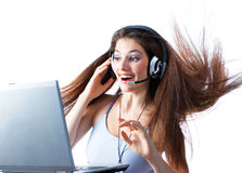 Working in a laptop. A girl with the head-phones working in a laptop royalty free stock photos