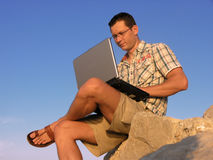 Working on laptop. Young man working on laptop outdoor stock photography