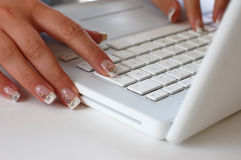 Working on Laptop. A woman with beautiful nails typing on a laptop Royalty Free Stock Photos