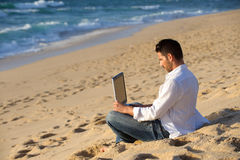 Working in the laptop at the beach Stock Photo