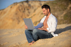 Working in the laptop at the beach Royalty Free Stock Image