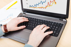 Working with laptop and graph on screen at table Royalty Free Stock Images