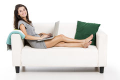 Working with a laptop at home. Beautiful woman on a sofa working with a laptop, isolated in white Royalty Free Stock Photography