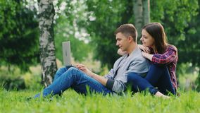 Starting working on the laptop. The man opens the screen of a laptop, sitting on the grass in the park, woman hugging stock video