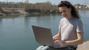 Working with a laptop outdoors. Girl with a laptop by the river. A spring sunny day. stock footage