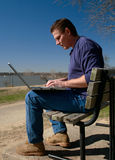 Working on Laptop in Park. Businessman, dressed in casual clothes for the weekend, still works into the late afternoon on his Royalty Free Stock Images