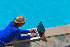 Working on laptop at the pool Stock Photo