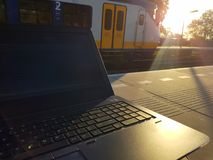 Working on laptop while waiting on platform for train, maximize productivity. Working on a mobile workstation or laptop, while waiting on the platform for the stock images
