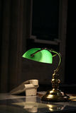 Working Late. Old fashioned desk lamp and telephone on a study table in a dark room Stock Image