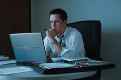 Working late. Young man working late on laptop in office Royalty Free Stock Image