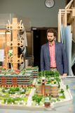 Working at layout. Young architect in formalwear looking at layout of modern city with new buildings and streets Stock Image