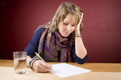 Working on List. Pretty, young woman studying in a home environment Stock Photography