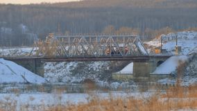 Working locomotive passes through a railway bridge. Winter landscape stock footage