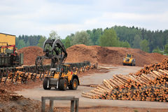 Working at Lumber Yard. KYRO, FINLAND - JUNE 7, 2014: Volvo L180F High Lift wheel loader working at mill lumber yard.  The arm is capable of reaching a lift Royalty Free Stock Images