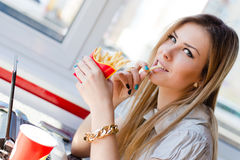 Working lunch: image of drinking & eating fries beautiful young business lady blond girl having fun working on laptop Royalty Free Stock Photos