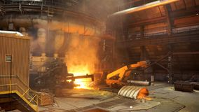 Working machine at metallurgical plant, molten steel production. Stock footage. Hot steel on conveyor in steel mill. Working machine at metallurgical plant stock photos