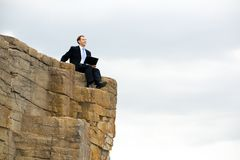 Working man. Image of businessman sitting on rocky stones with laptop on his knees Royalty Free Stock Image