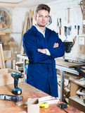 Working man demonstrating his workplace and tools. Smiling working man demonstrating his workplace and tools at a workshop Stock Image