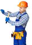 Working man with hammer driving a nail in wall Royalty Free Stock Photo