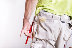 Working man holding red pencil. Man holding red pencil. Pockets full of tools Royalty Free Stock Images