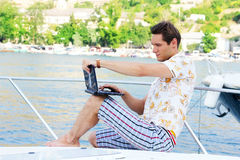 Working man with laptop sitting on white yacht Royalty Free Stock Photos