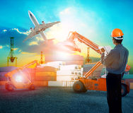 Working man in logistic business working in container shipping y. Ard with dusky sky and jet plane cargo flying above use for land to air transport and freight Royalty Free Stock Images