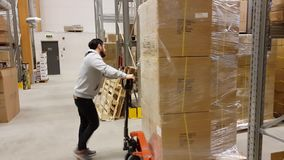 A working man moving cartons with fork lift truck in warehouse/store. Industrial.Transportation concept. stock footage